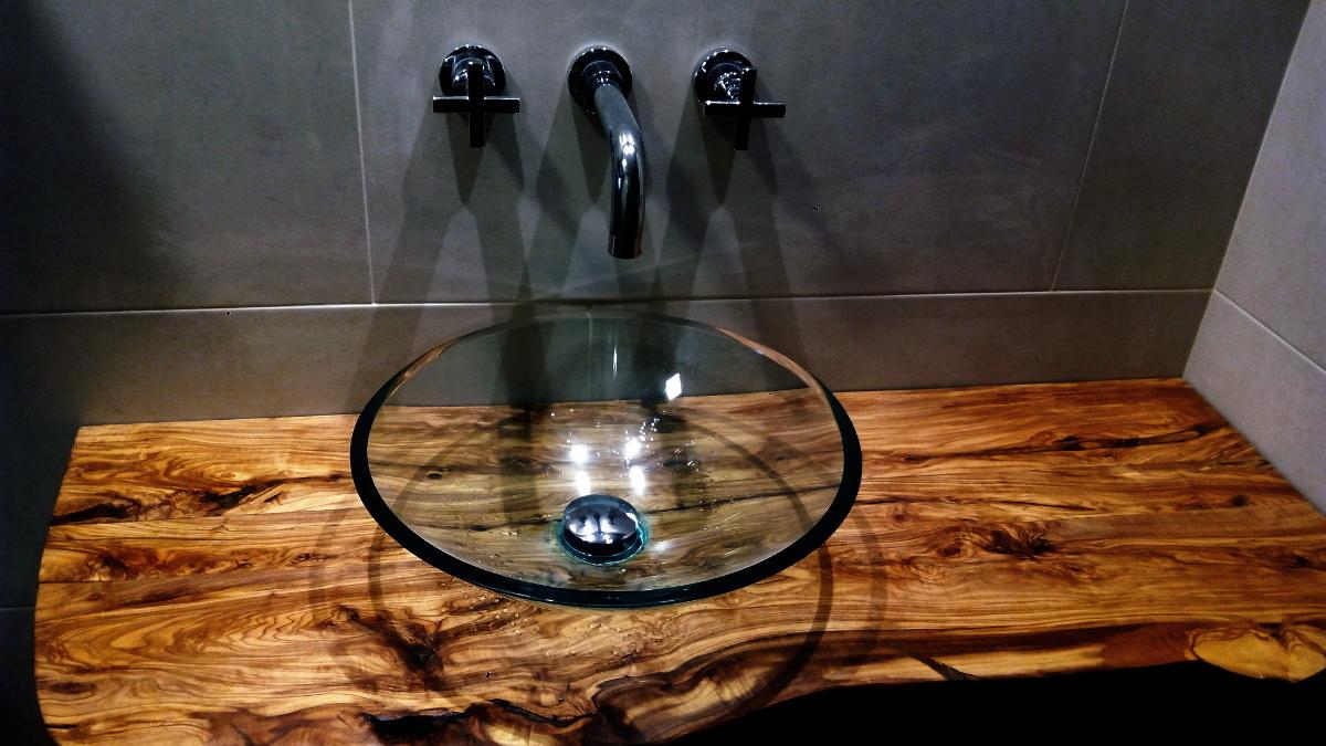 encimera de bao de madera en un bao moderno con lavabo del cristal